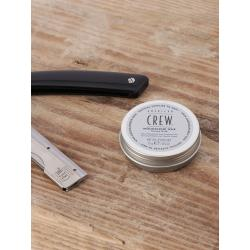 pot de cire à moustache american crew sur planche en bois à coté d'un rasoir couteau
