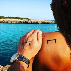 Plages de méditéranée avec le Mtattoo tatoué sur une épaule de femme et une main d'homme