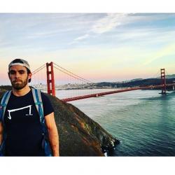 un homme qui porte un M tee shirt noir de la marque Aurelien Magnano devant le pont de San Francisco Californie USA