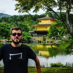 un homme qui porte un M tee shirt noir de la marque Aurelien Magnano devant un lac au japon