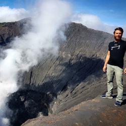 un homme qui porte un M tee shirt noir de la marque Aurelien Magnano  devant un volcan en Nouvelle zellande
