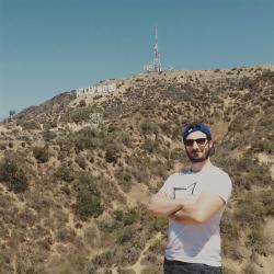 un homme qui porte un M tee shirt blanc de la marque Aurelien Magnano devant les lettres hollywood à los angeles Californie USA