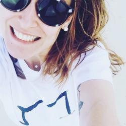 une belle jeune femme qui porte un M tee shirt blanc
