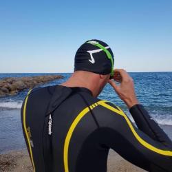 Le bonnet M par Aurélien Magnano - bonnet de piscine de la marque Aurelien Magnano Sur un nageur de triathlon face à la mer