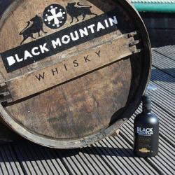 Whisky Notes Fumées-BLACK MOUNTAIN-bouteille posée sur une terrasse à coté d'une barique de whisky Black Mountain